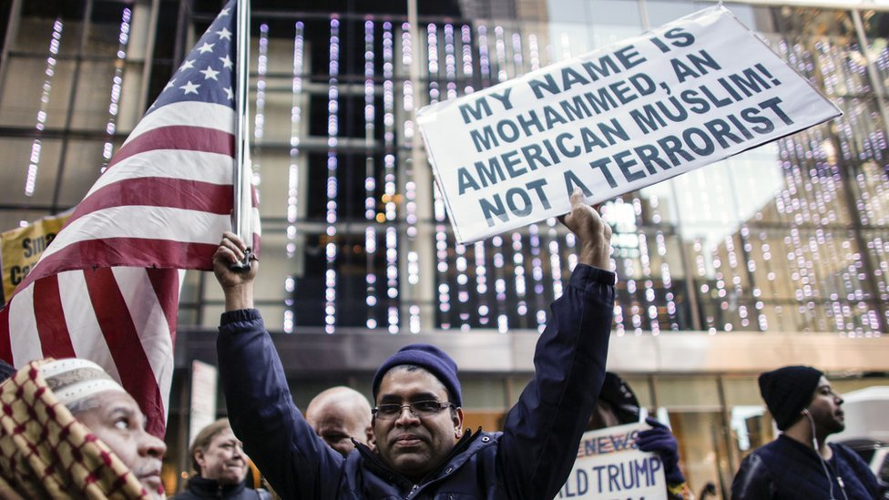 "An American Muslim holds up a ""not a terrorist"" placard"