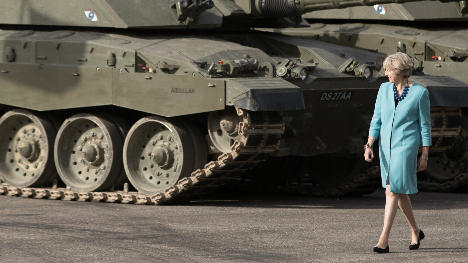 Theresa May walking by a tank