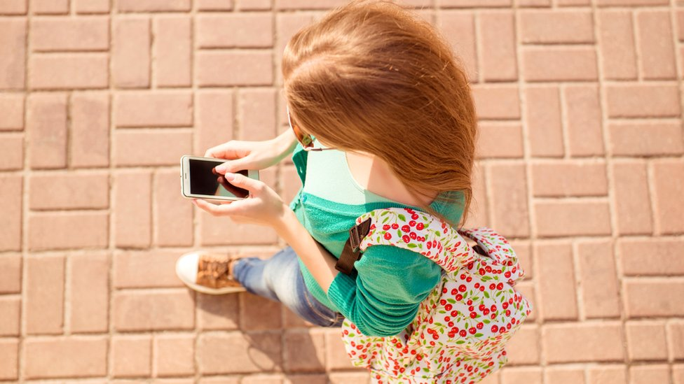 Mujer joven andando por la calle con el celular.