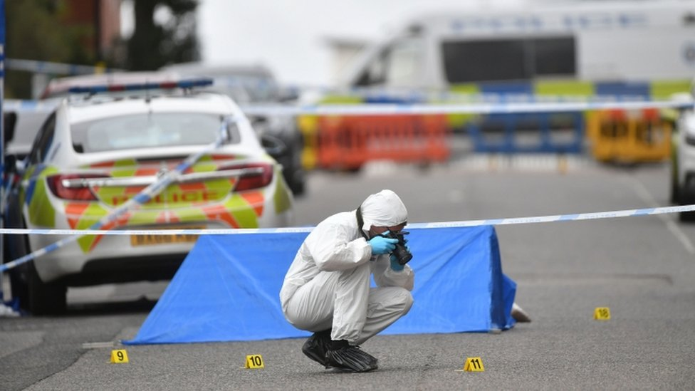A police forensics officer taking photographs in Irving Street