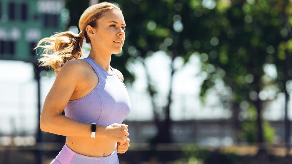 Woman running while wearing a Fitbit device