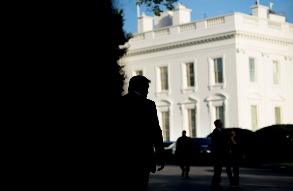 Donald Trump silhouetted against the White House