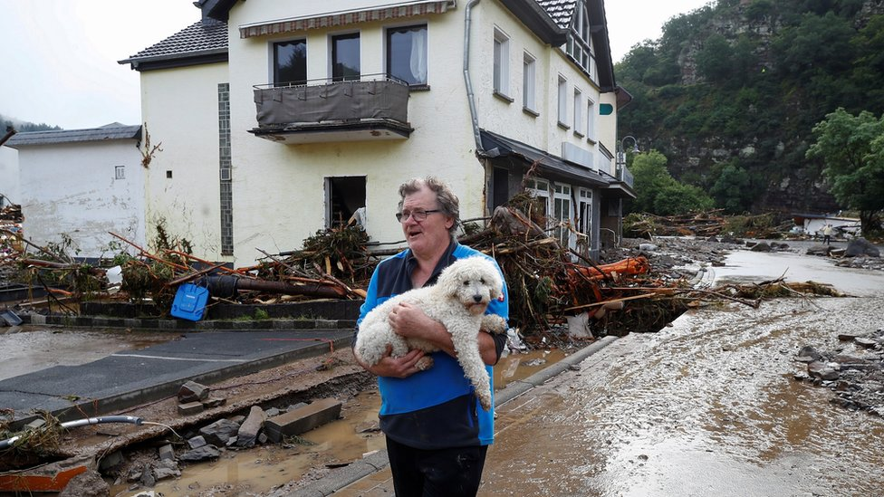 A man carries a dog next to debris brought by the flood