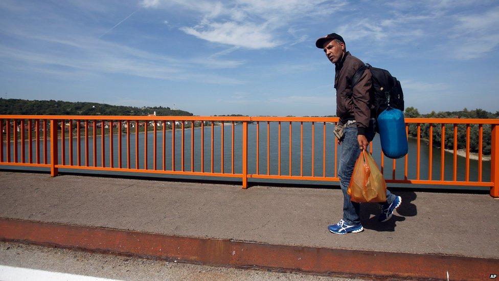 A migrant walks on road bridge over the Danube river between Serbia and Croatia, near Batina, Croatia, Thursday, Sept. 17, 2015