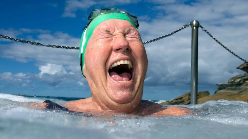 An elderly woman laughs in a hot tub