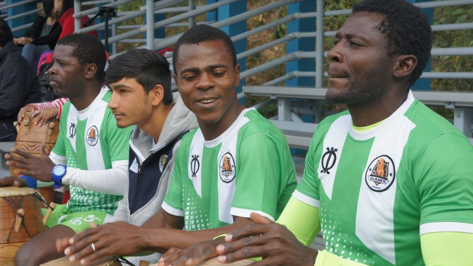 Team captain Darius (centre) and founder Medard (right) sit next to two other football club players