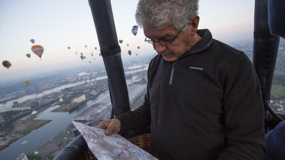 Hot air balloon pilot Phil Langdon checks a map while flying over London
