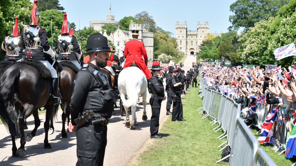 Crowds cheer for Prince Harry, Duke of Sussex, and his wife Meghan, Duchess of Sussex