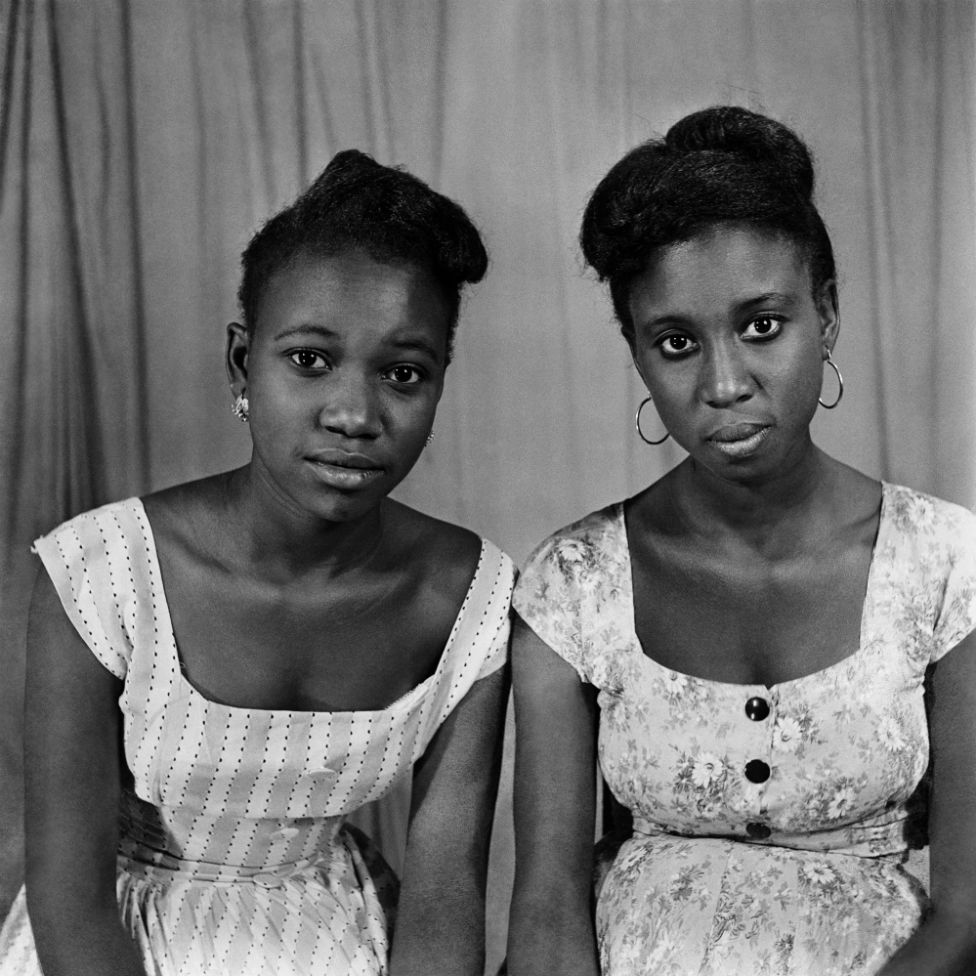 Two women pose for the camera in the photographer's studio.