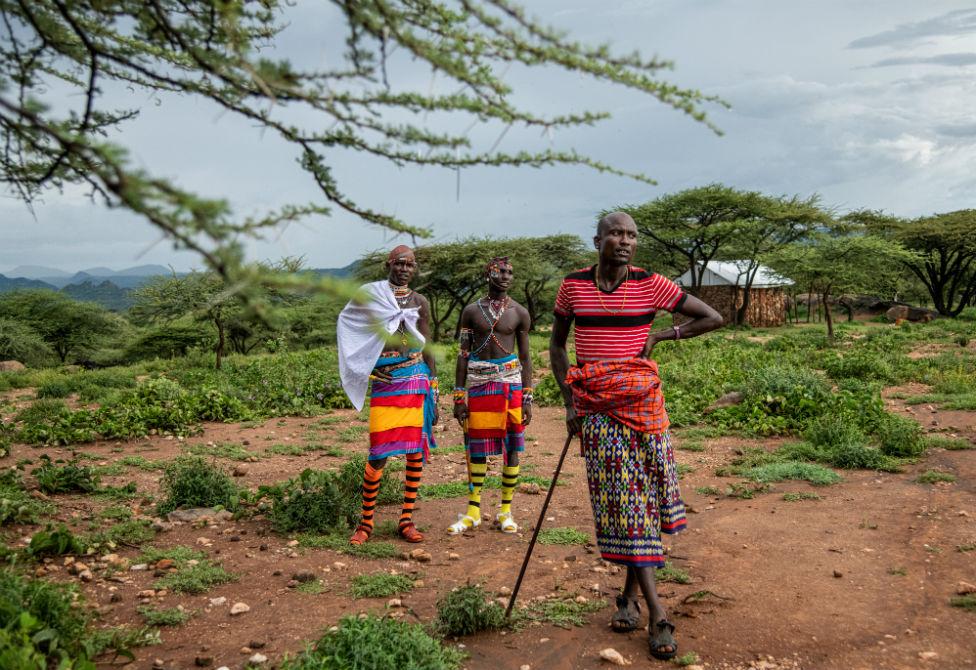 Two Samburu warriors talk to Tiampati Leletit, who lost 80 of his goats when the locusts arrived