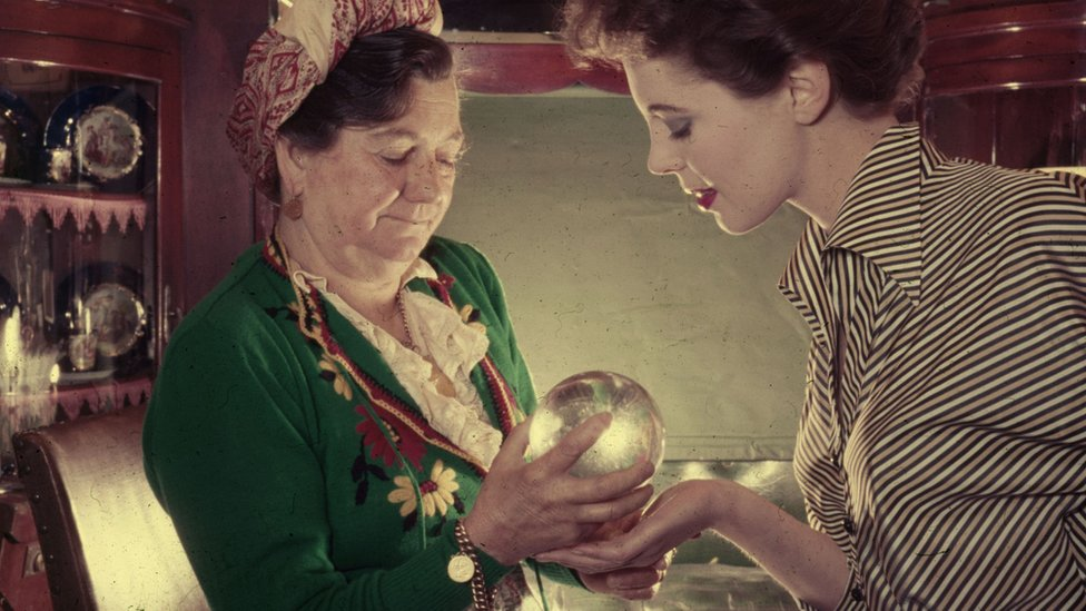 A gypsy fortune teller looking at a crystal ball c.1970