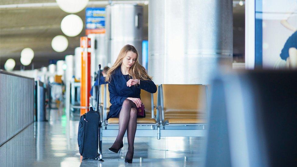 Una mujer mira su reloj en un aeropuerto.