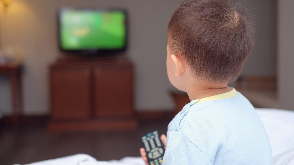 Niño mira la televisión.