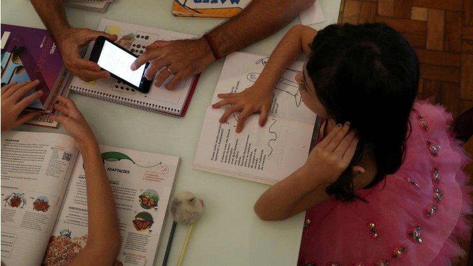 Niños haciendo deberes con un celular en medio