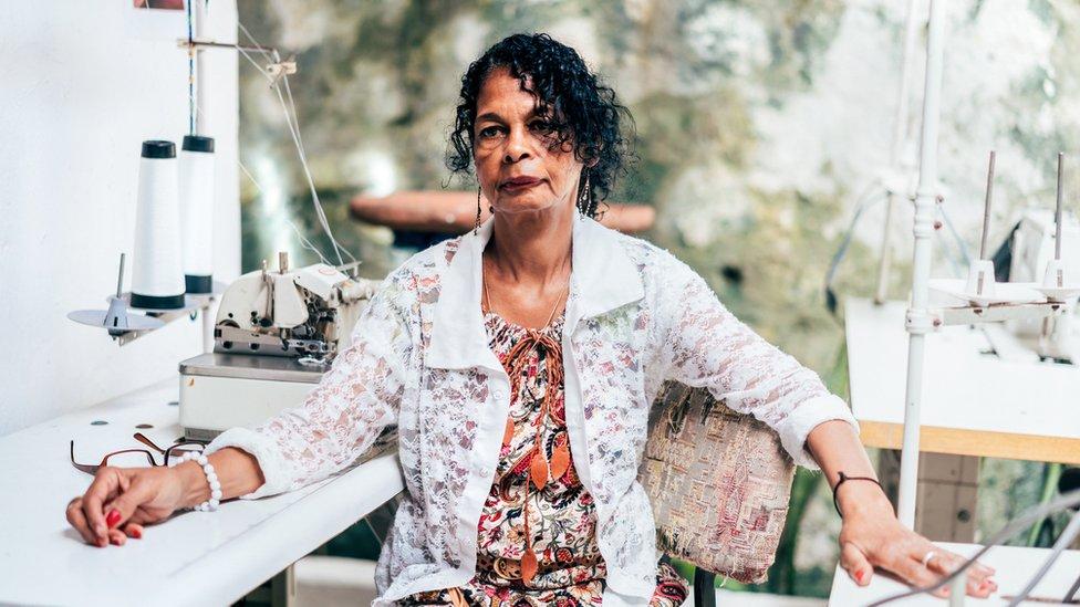 Mujer sentada junto a máquina de coser.