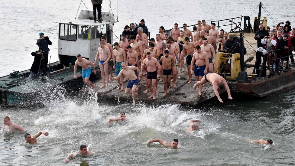 Serbian Orthodox faithfuls jump into the cold water of the Sava river in Belgrade