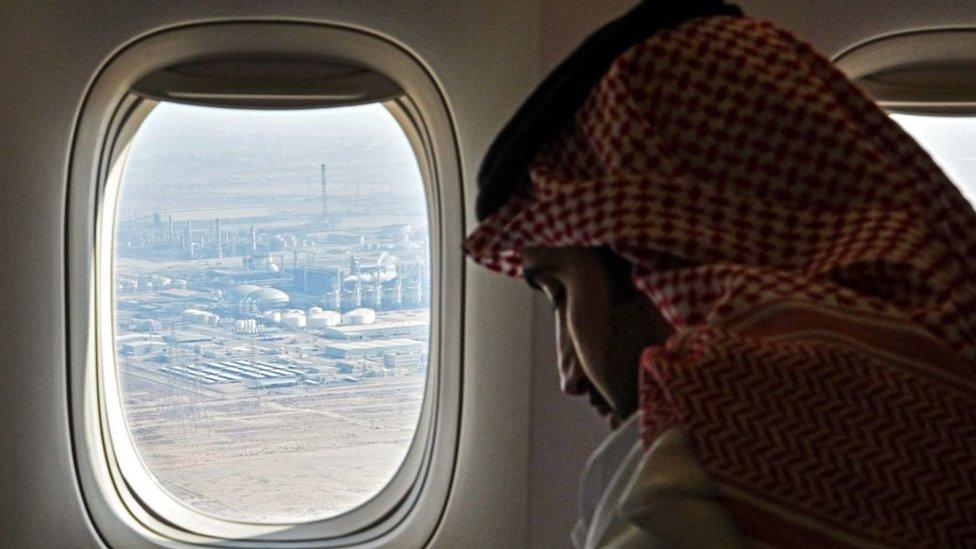 Un hombre en un avión desde el que se ve una instalación petrolera en la ciudad industrial de Jubail, Arabia Saudita