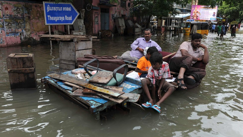 Indian residents sit on wooden pallets in floodwaters in Chennai