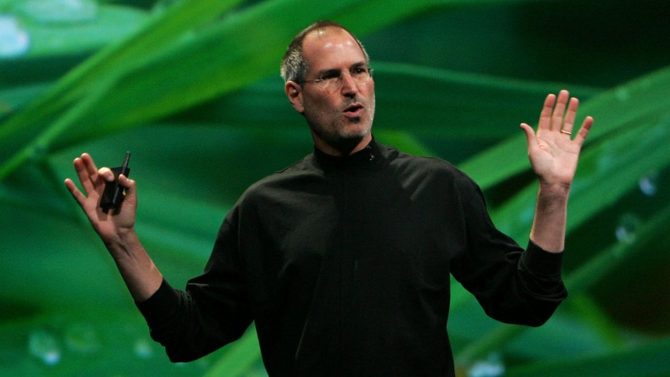 Steve Jobs standing in front of an image of leaves with water droplets