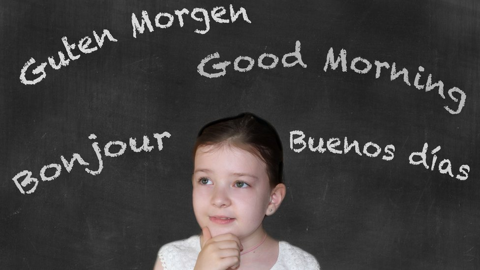 A girl with a board with a good day's word in several languages.