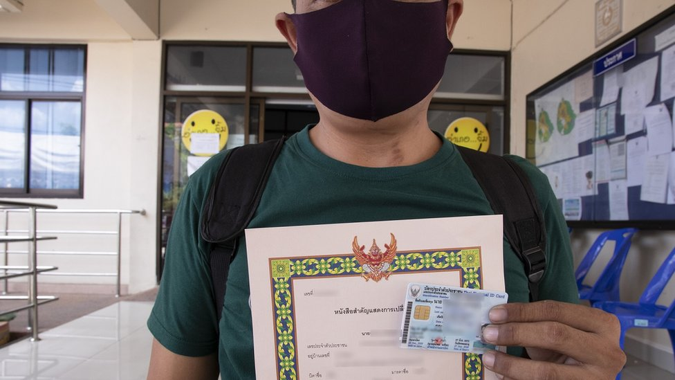Ek holds up a document and ID card