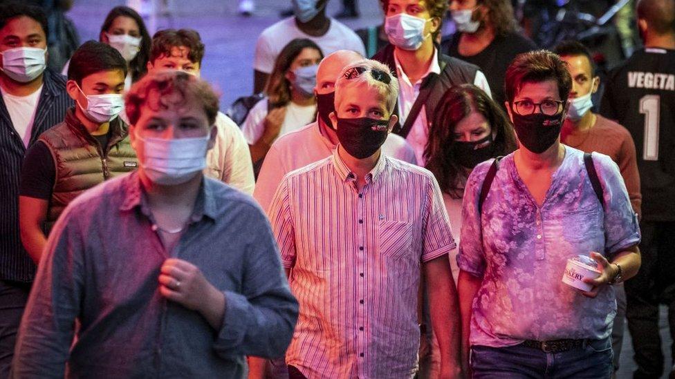 Amsterdam'da maske ile sokakta yürüyen insanlar.