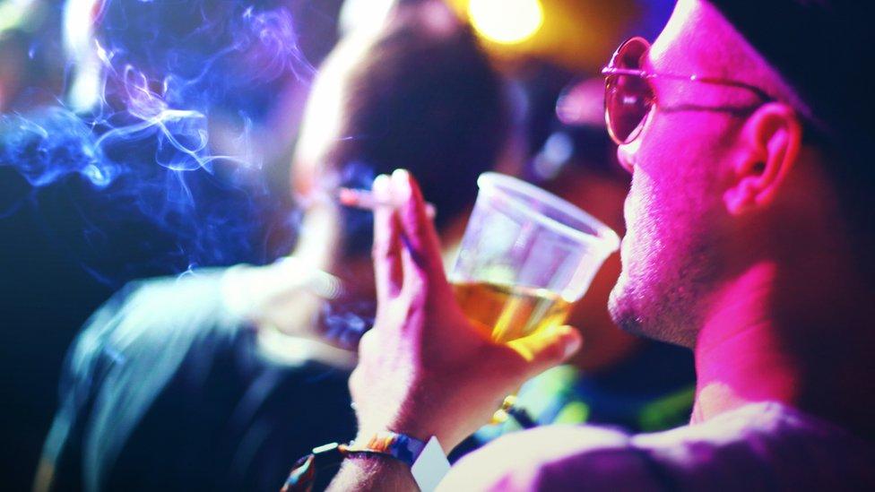Hombre bebiendo y fumando.