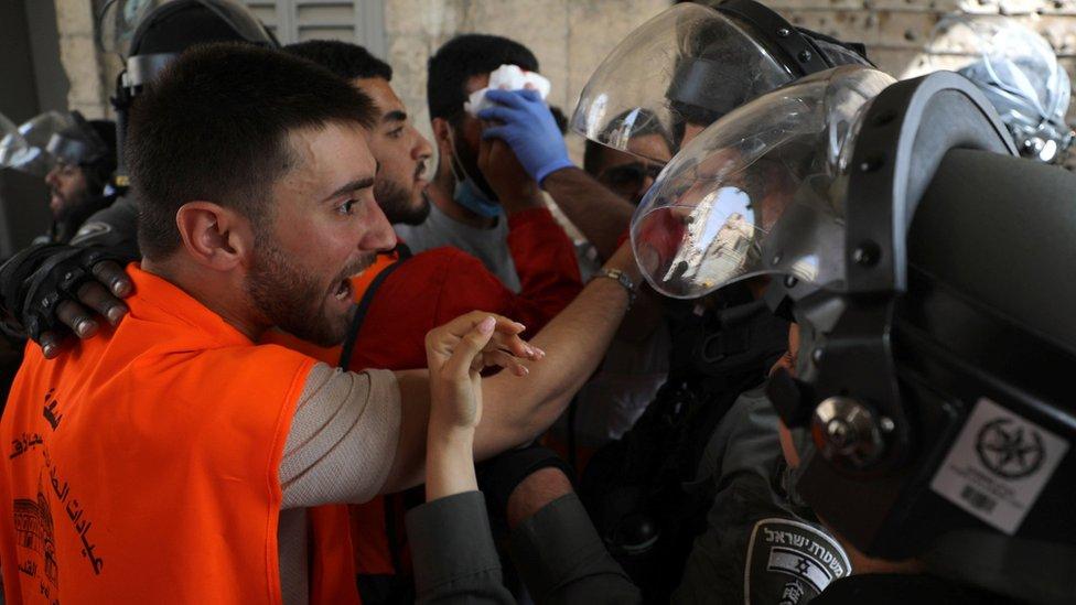Seorang petugas medis Palestina berdebat dengan polisi Israel dalam bentrokan di luar Masjid Al-Aqsa