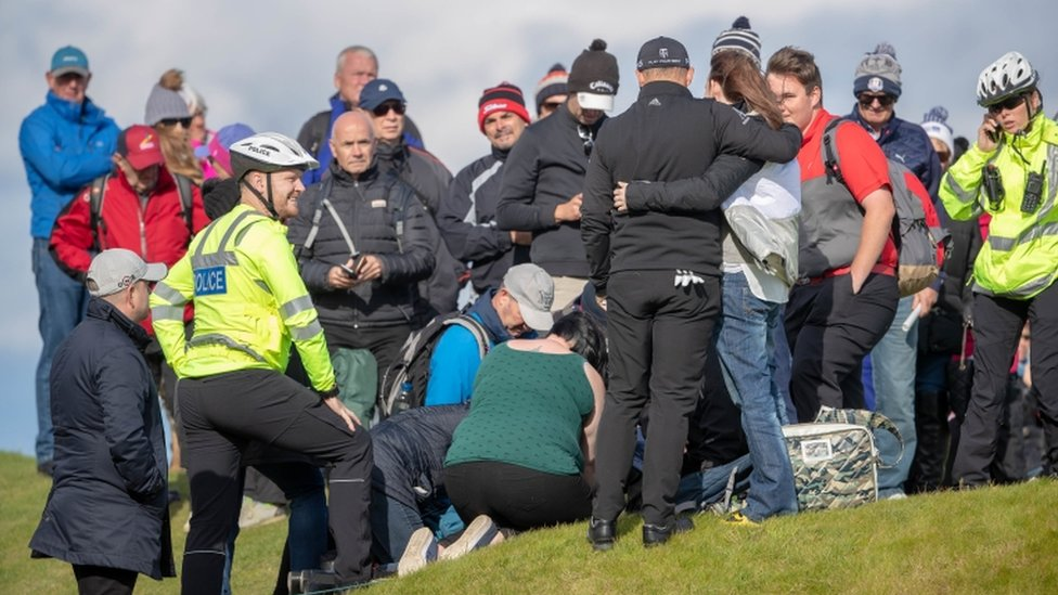 Police and first aiders attending to spectator