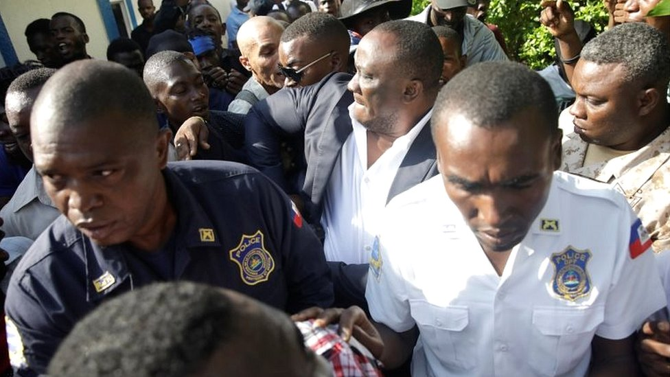 Haitian Senator Willot Joseph scuffles with opposition supporters as he arrives at Congress