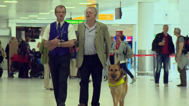 Ian and his guide dog are assisted in Glasgow airport