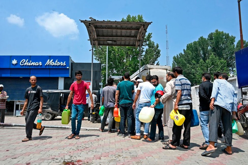 Residents stand in a queue as they hold empty cans to get filled at a petrol station in Srinagar on August 4, 2019