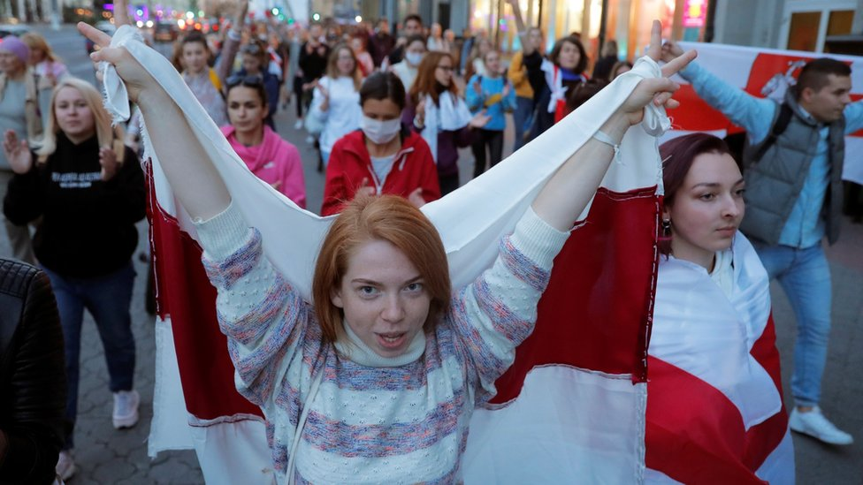 A woman carries a historical white-red-white flag of Belarus during an opposition demonstration against presidential election results in Minsk.