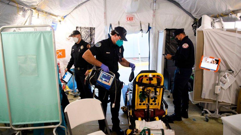 Sala de emergência improvisada dentro de uma tenda em hospital de Los Angeles; paramédicos circulam pelo local