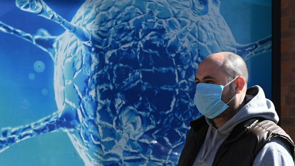 A man in a mask walking in front of the magnified image of a virus.