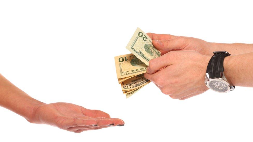 Hombre dándole plata a una mujer