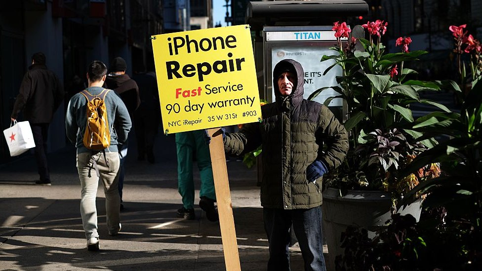 Un hombre sostiene un aviso de reparación de iPhones