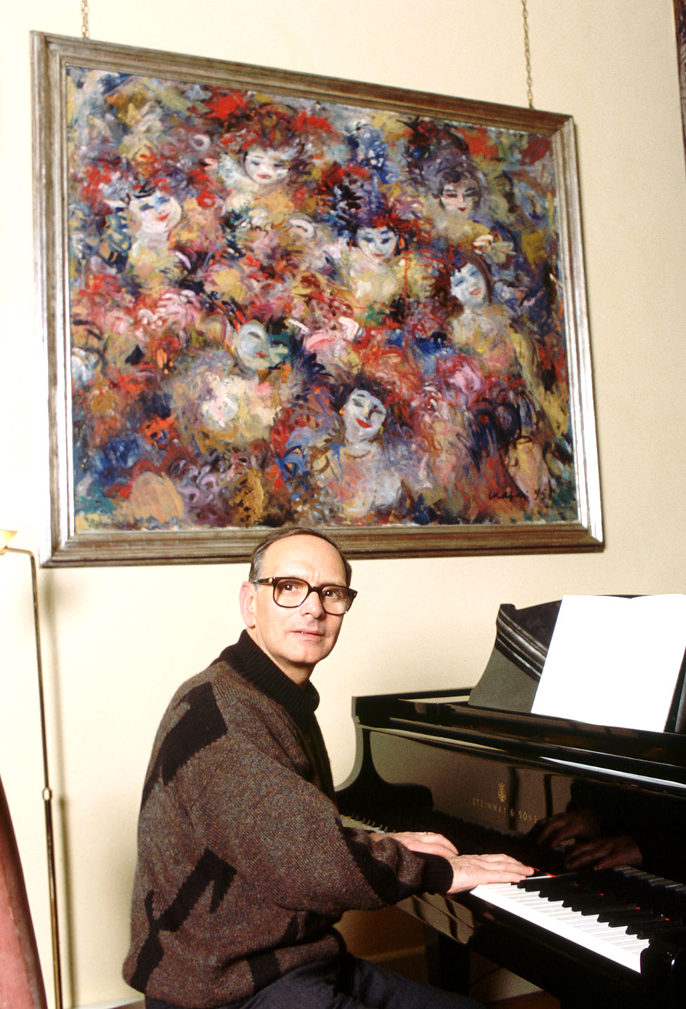 Ennio Morricone sitting at a piano with a large painting on the wall
