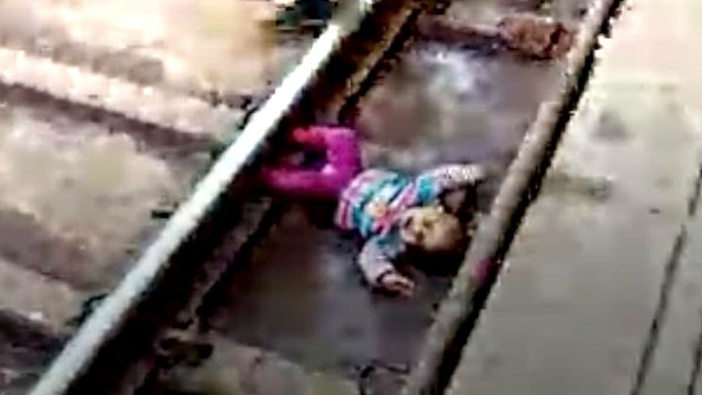 Baby in India narrowly escapes being hit by speeding train