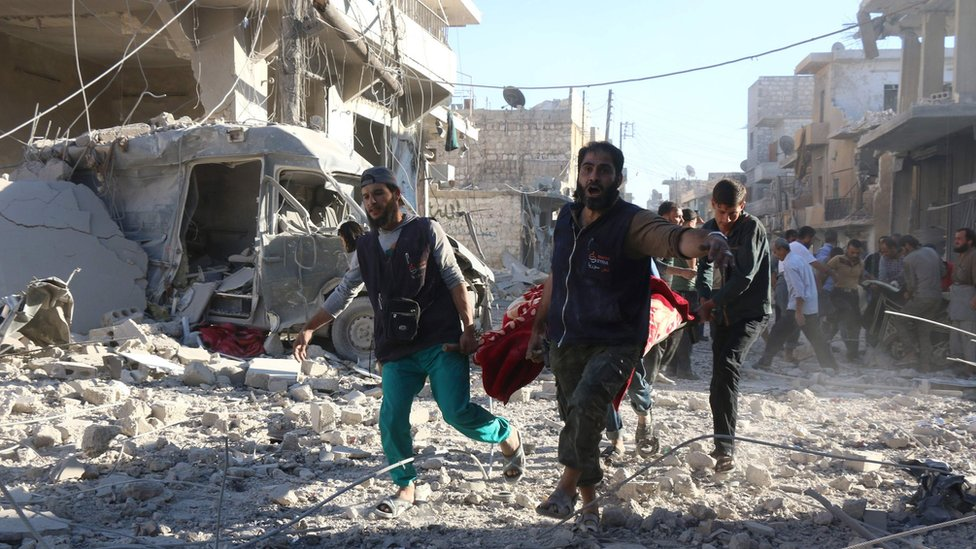 Syrian volunteers carry injured person on a stretcher following Syrian government air strikes on rebel held neighbourhood of Heluk in Aleppo, on September 30, 2016.