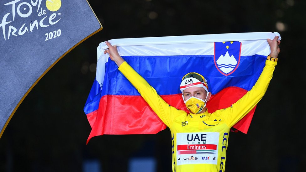 Tadej Pogacar holds up the Slovenian flag in celebration after winning the 2020 Tour de France
