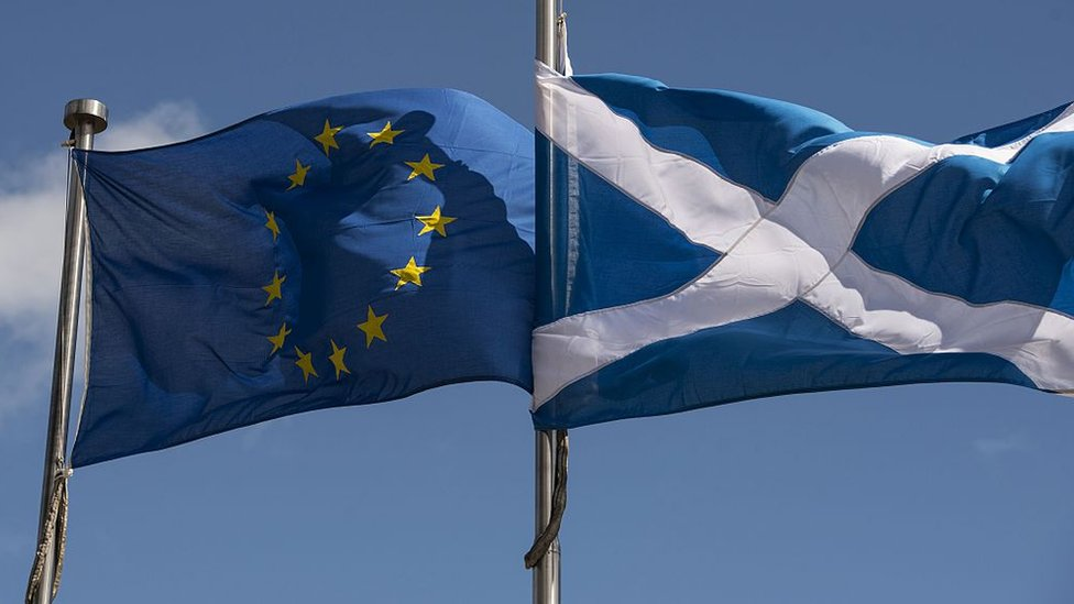 A Scottish Saltire (R) and a European Union (EU) flag fly in front of the Scottish Parliament