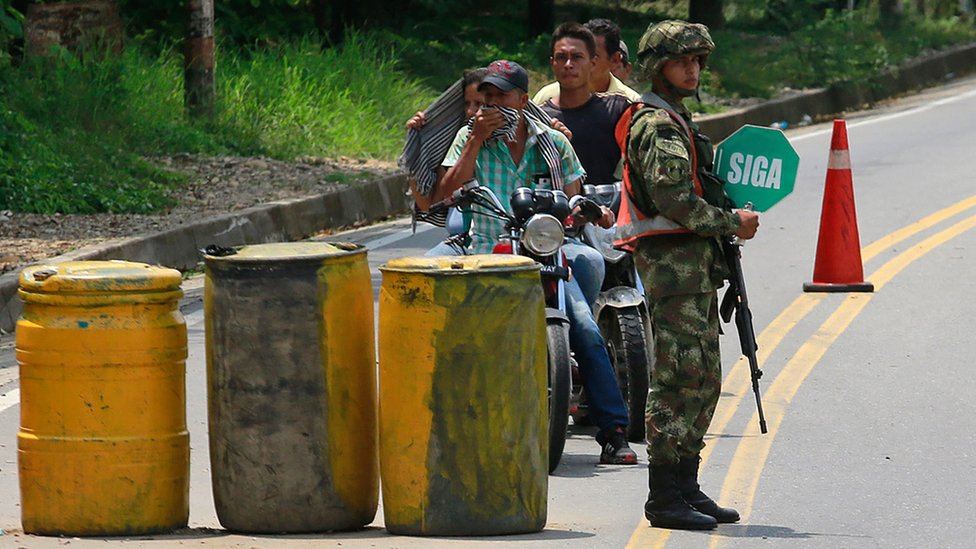 A soldiers stands guard in a streets of Tibu, in the region of Catatumbo, Norte Santander Department, in north-eastern Colombia, talk to a woman and a girl on April 27, 2018.