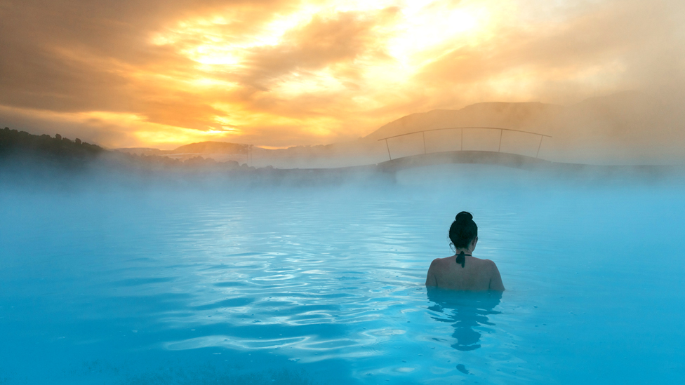 Rear view of a woman standing in the Blue Lagoon, Iceland