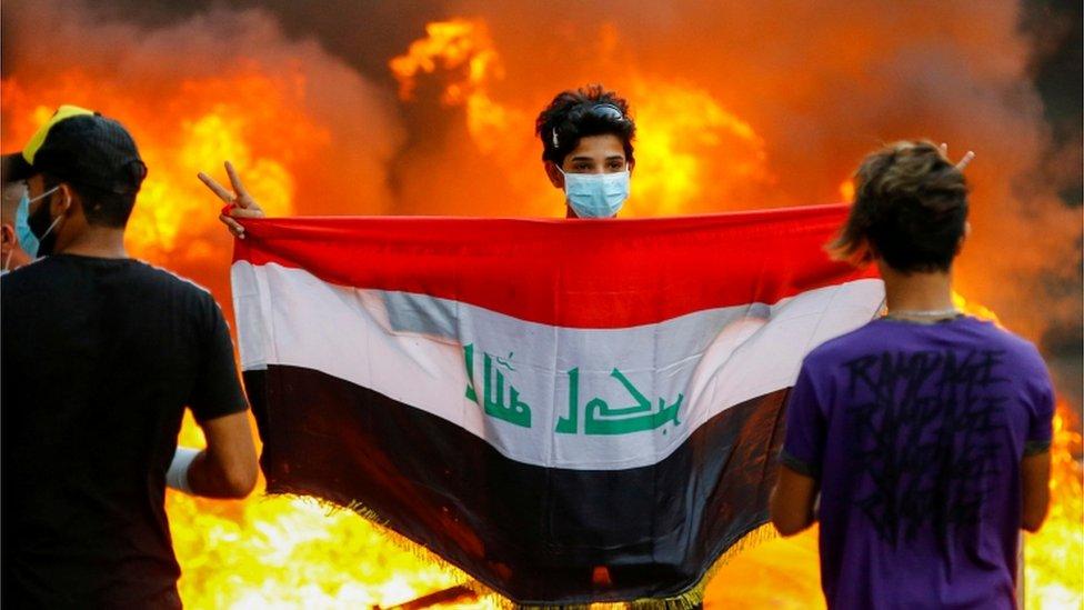 شاب عراقي يحمل العلم العراقي.