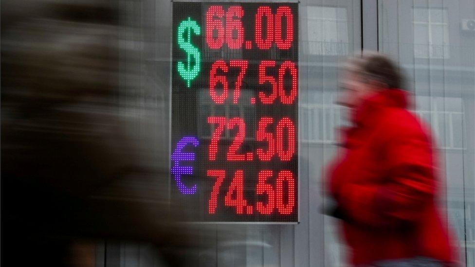 Mujer junto a un panel con la cotización del euro y el dólar.
