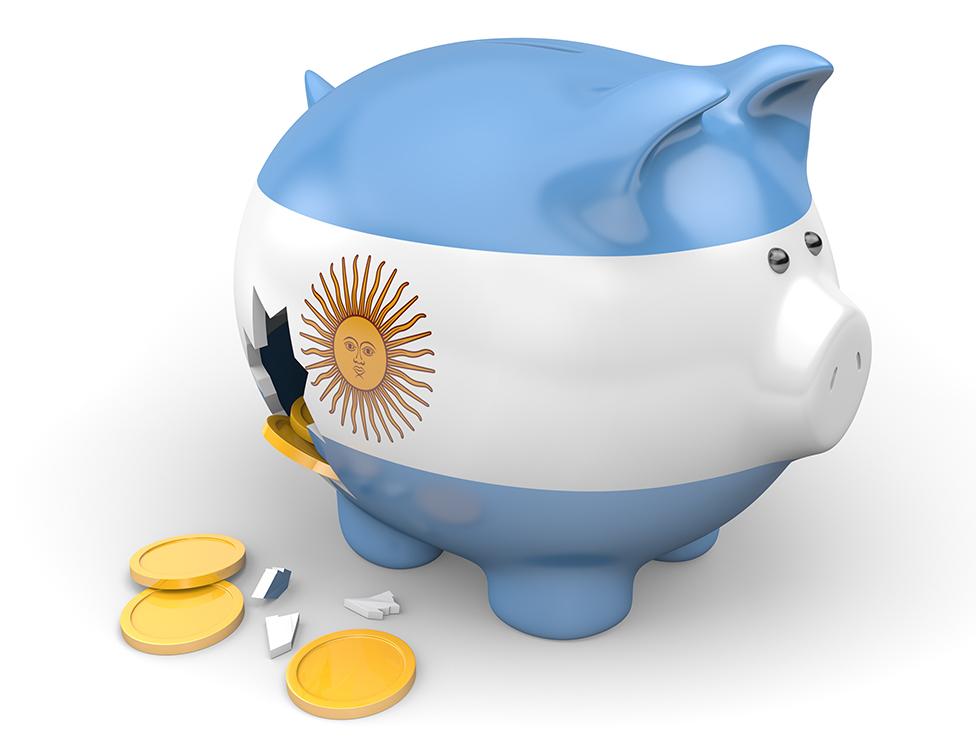 Un chanchito roto con los colores de Argentina y monedas salidas