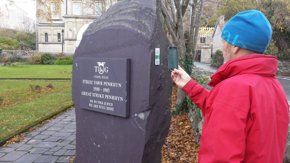 Strike memorial stone in Bethesda with a HistoryPoints QR code being scanned by a ma using a phone