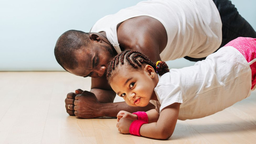 Un padre practica ejercicios con su hija