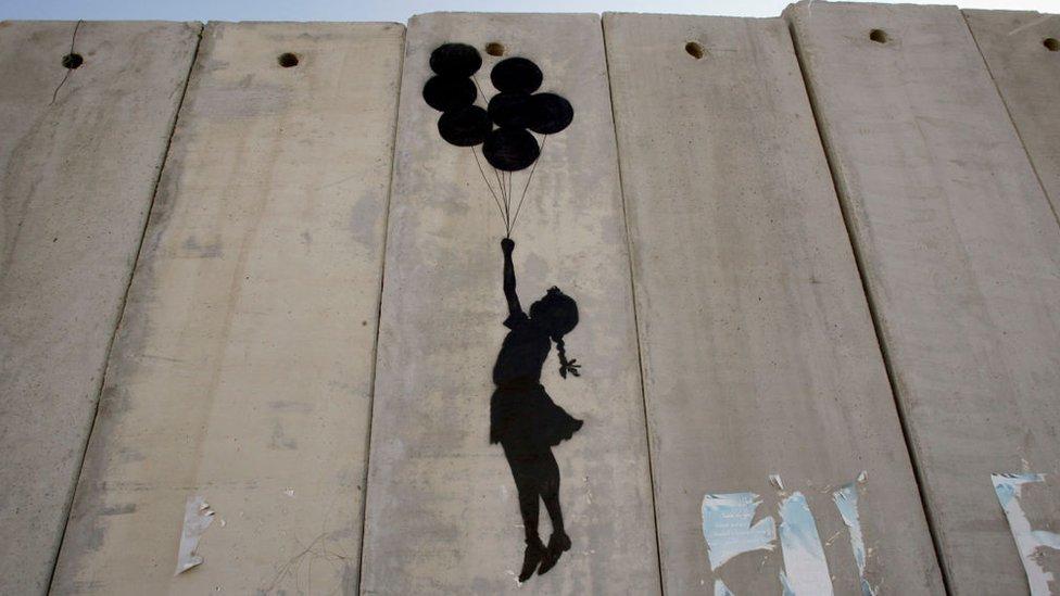 Obra de Banksy en el muro separador de Israel muestra la silueta de una niña elevada con unos globos